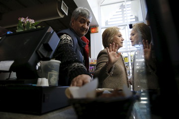 Clinton (R) politely declines to eat more cake samples, after having tried the coconut pound cake and purchasing items to go from Rahnamoon as she greets people at his cafe in Charleston, South Carolina