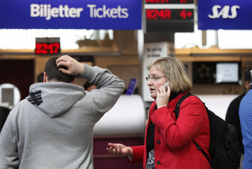 Travelers wait to speak to an SAS ticket agent as flights continued to be delayed and cancelled at Stockholm's Arlanda Airport