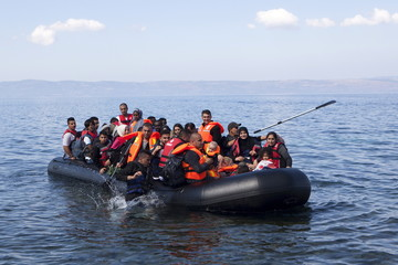 Refugees and migrants arrive in an overcrowded dinghy on the Greek island of Lesbos after crossing a part of the Aegean Sea from the Turkish coast