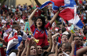 Costa Rican soccer fans celebrate while watching a large screen broadcast of the 2014 World Cup match in San Jose