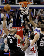 Spurs guard Parker shoots a reverse layup near 76ers forwards Brand and Iguodala during the fourth quarter of their NBA basketball game in Philadelphia