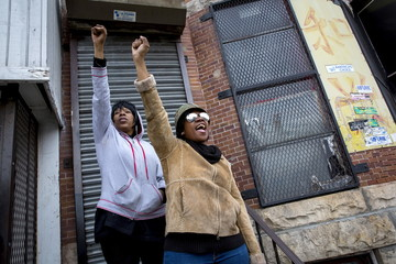 People react as police line North Ave and Pennsylvania Ave in Baltimore, Maryland