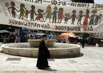 An Orthodox priest walks past a banner at Constitution (Syntagma) square in Athens