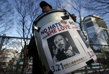An anti-racism protester holding a drum which has a picture of Martin Luther King, Jr. poses for photographs before a march in Tokyo