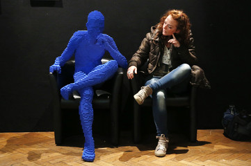 """A visitor poses beside the art work titled """"Blue Guy Sitting"""" during """"The Art of the Brick"""" exhibition in Brussels"""