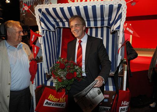 Former general secretary of the left-wing Die Linke party Bartsch poses in front of the beach chair he received as a present at a party congress in Rostock