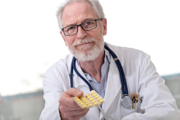Portrait of doctor giving pills