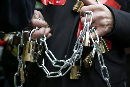 Locks and chains are held by a man who participates in the protest march by the heads of small and mid-size French companies in Paris