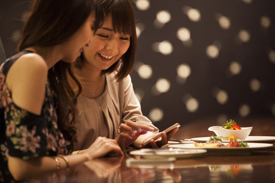 Women are watching smartphones while eating at the bar