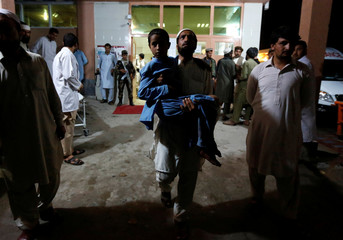 An Afghan man carries a slightly wounded boy after a blast, at a hospital in Jalalabad, Afghanistan