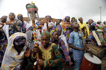 Devotees of the river goddess Osun dance down a street during the traditional town cleansing procession at the start of the annual Osun festival in Osogbo in Nigeria's southwest