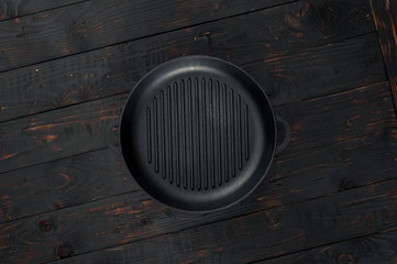 Vintage empty grill pan on dark wooden table close up