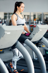 Strong young and beautiful woman runs on treadmill in the gym. Concept of a healthy lifestyle and sport