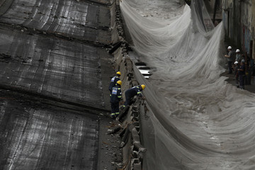 Construction workers remove debris after the demolition of Perimetral overpass in Rio de Janeiro