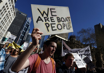 Man holds a placard during a protest against the Australian government's policy on asylum-seekers in central Sydney