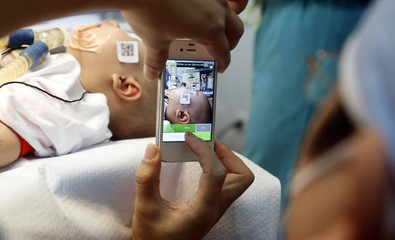 A doctor uses a smartphone to take a photo of a child with facial deformity before surgery at the Vietnam Cuba hospital in Hanoi