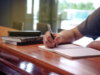 Close up image of student writing on a coffee mug on a coffee table