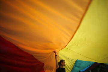An activist touches a rainbow flag during the fourth Sofia Pride annual parade in Sofia