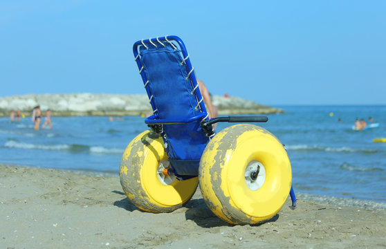 Special wheelchair with large yellow inflatable wheels to bring disabled people inside the water of ocean