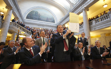 Herbert holds up the SB296 bill that he signed at the state capitol in Salt Lake City