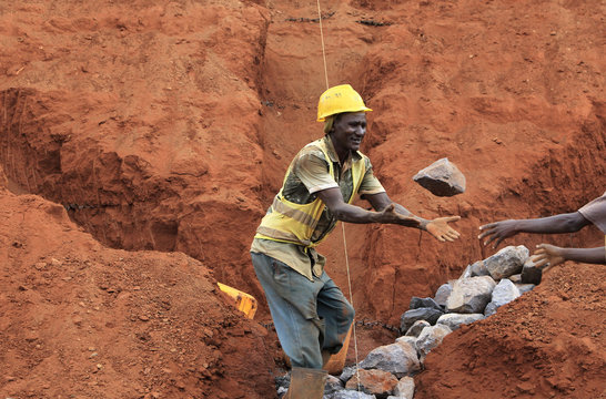Construction workers pass each other rocks as they work at a landscaping section of the Mombasa-Nairobi standard gauge railway near Emali