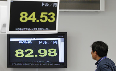 A foreign exchange broker watches a television showing the Japanese yen's exchange rates against the U.S. dollar in Tokyo