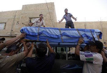 Residents place the coffin of a victim from Thursday's bomb attack on a minibus during a funeral in al-Shurta al-Rabaa district in Baghdad