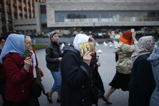 Ukranian Orthodox Christians walk while holding religious icons outside a regional government building in Donetsk