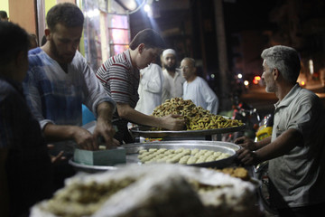 Men sell traditional sweets on the eve of Eid al-Fitr in the Idlib countryside