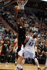 Miami Heat forward Bosh shoots over Minnesota Timberwolves forward Love in Minneapolis