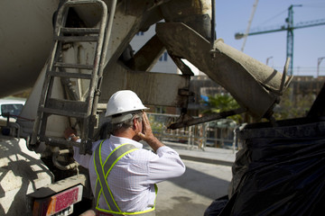 A cement truck driver gestures in front of a construction site in Tomares