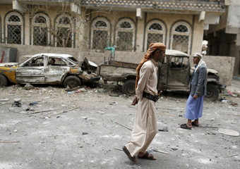 People walk at the site of Monday's car bomb attack in Yemen's capital Sanaa