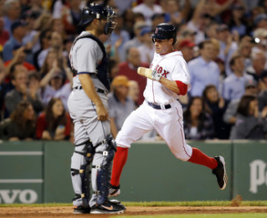 Boston Red Sox's Podsednik scores run behind Detroit Tigers catcher Avila on three RBI hit by Red Sox's Nava during their American League baseball game in Boston