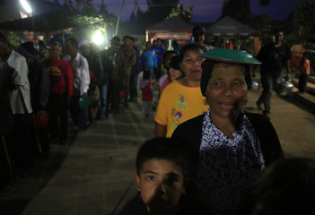 A villager places plates on her head while standing in queue for dinner after being evacuated from her home due to the eruption of Mount Sinabung, at a temporary shelter in Kabanjahe