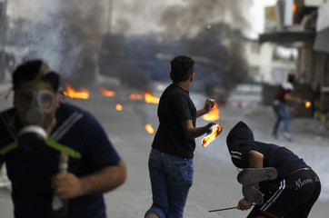 Anti-government protesters throw petrol bombs towards riot police during clashes in the village of Diraz