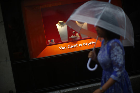 A woman walks past a high-end retail store along 5th Avenue in New York