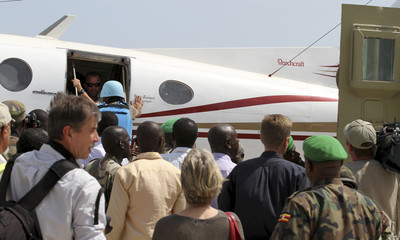 People stand around the plane carrying released British hostages Paul and Rachel  Chandler as they arrive at the airport in Somalia's capital Mogadishu