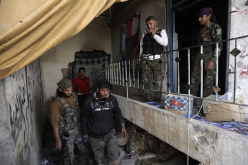 Free Syrian Army fighters carry their weapons as they move inside a building in Deir al-Zor, eastern Syria