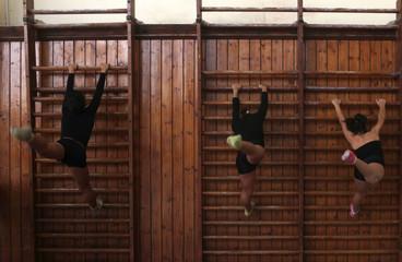Young girls train inside a gymnastics hall in Alexandria