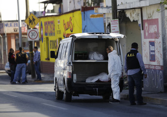 A member of a forensic team and a police detective stand next to the coroner's vehicle at a crime scene in Monterrey