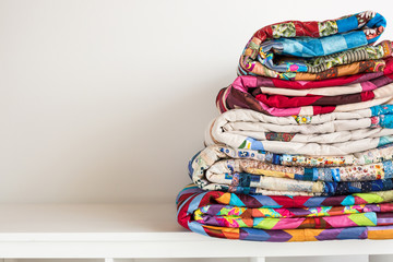 sewing and fashion concept - stack of colorful quilts, beautiful bedspreads stacked in several rows in height for storage, sale patchwork productions on a white background, copy space Fototapete