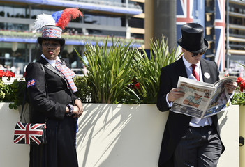 A race goer reads a paper whilst another leans on a wall on Ladies Day at Royal Ascot, just south of London