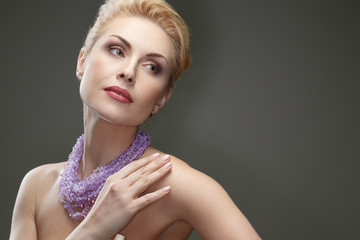 Face of elegance. Studio shot of a gorgeous mature woman wearing necklace posing on grey background
