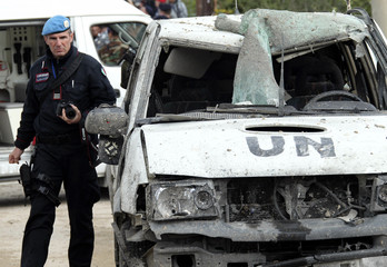An Italian military expert inspects a damaged U.N. vehicle on the outskirts of the city of Tyre