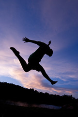Silhouette happy jumping against beautiful in sunset. Freedom, enjoyment concept