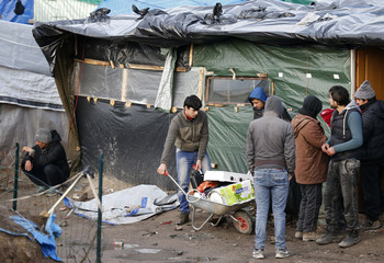 """Migrants use a wheelbarrow to transport their affairs during the partial dismantlement of the camp called the """"jungle"""", in Calais"""