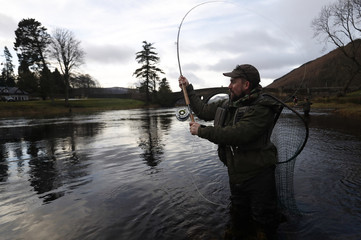 An angler fishes on the opening day of the salmon fishing season on the River Tay at Kenmore in Scotland