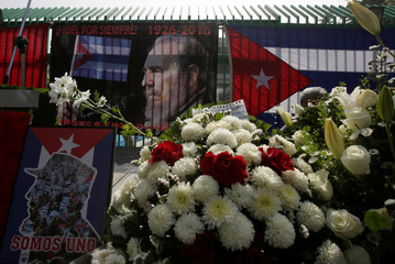 Cuban flags, pictures of Fidel Castro and flowers are seen during a tribute ceremony outside the Cuban Embassy in Mexico City