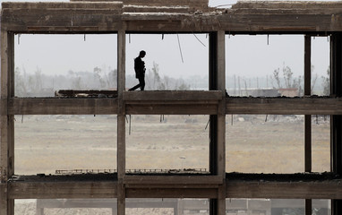 A member of the Iraqi security forces walks with his weapon in the building on the outskirts of Falluja
