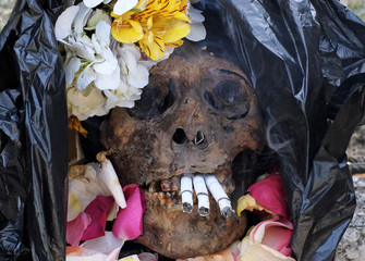 "A skull is seen with cigarettes and decorated with flowers during the ""Dia de las natitas"" (Day of the Skull) celebrations at the General Cemetery of La Paz"